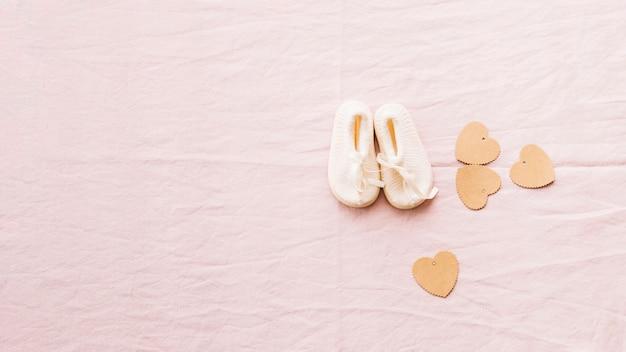 Adorable bebé-zapatos y corazones de papel