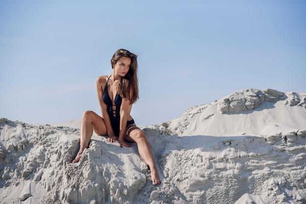 Adorable chica deportiva en traje de baño negro en la playa de verano.