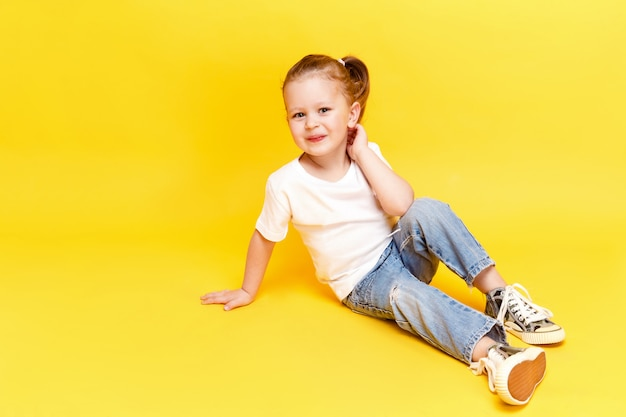 Adorable chica elegante posando en amarillo