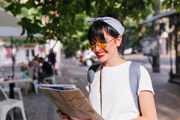 Adorable chica morena con sonrisa de hollywood mirando el mapa de la ciudad en busca de destino de pie en medio de la calle