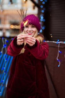 Adorable chica rubia sosteniendo brillantes luces de bengala en la feria de navidad en kiev. efecto de desenfoque
