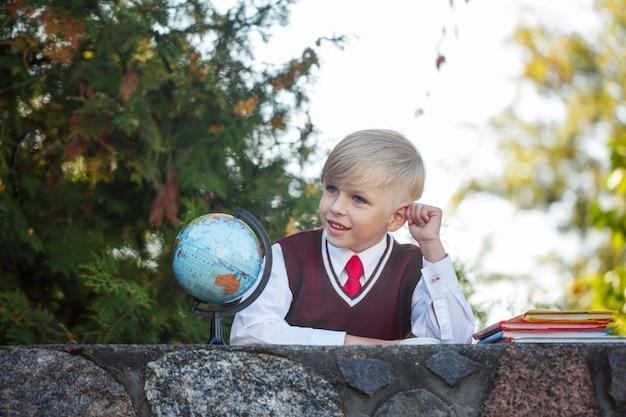 Adorable colegial con libros y globo en el exterior. educación para niños. volver al concepto de escuela.
