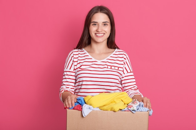 Adorable dama vistiendo ropa casual posando aislado sobre rosy studio wall