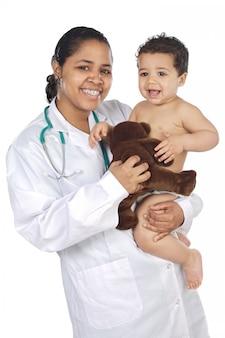 Adorable doctor con un bebé en sus brazos sobre fondo blanco