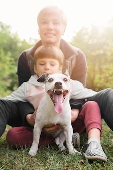 Adorable familia jugando con perro en el parque