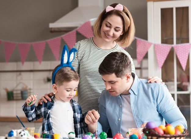 Adorable familia con niño pintando huevos