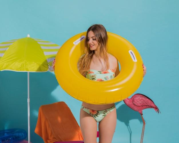 Adorable hembra joven sosteniendo un círculo de natación