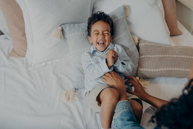 Adorable hijo acostado sobre almohadas en la cama y riendo mientras mamá le hace cosquillas