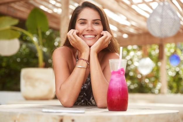 Adorable joven con amplia sonrisa descansa en el bar durante el día de verano, bebe batido de frutas exóticas, disfruta de un buen descanso en un cálido país exótico. mujer muy sonriente recrear en restaurante en la acera.