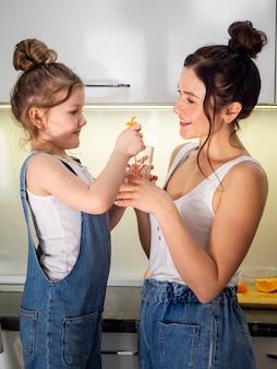 Adorable joven compartiendo jugo de naranja con madre