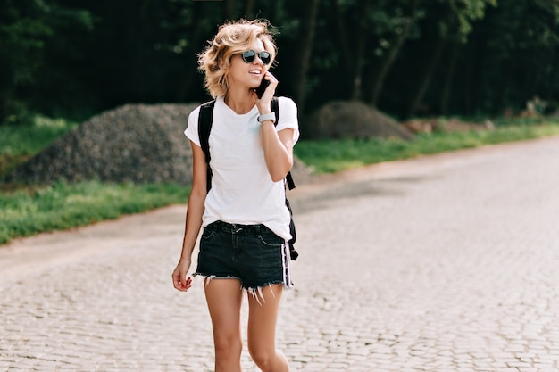 Adorable joven encantadora con peinado corto caminando por la carretera con mochila y hablando por teléfono sobre las montañas. estado de ánimo de viaje, vacaciones, viaje. pasión por los viajes y concepto de viaje.