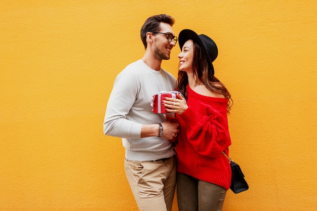 Adorable joven pareja enamorada. chico guapo le da un regalo a su amor