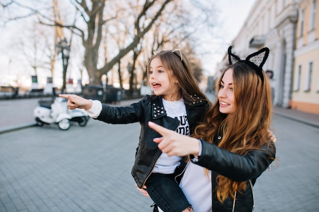 Adorable joven con su hija vio algo interesante al otro lado de la calle. niña sorprendida en chaqueta de cuero que señala el dedo en el punto de referencia junto a la hermosa mamá.