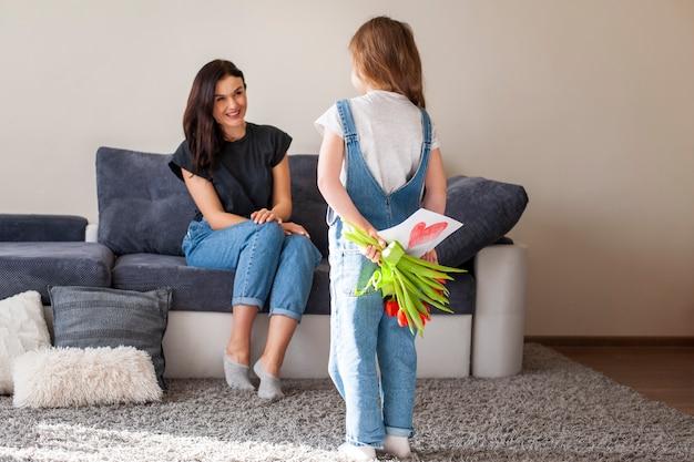 Adorable jovencita sorprendente madre con regalos
