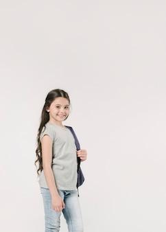 Adorable junior con mochila en estudio
