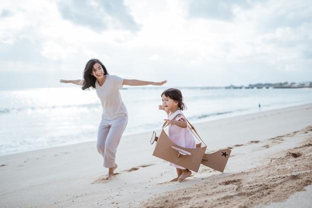 Adorable madre e hija jugando con avión de juguete de cartón
