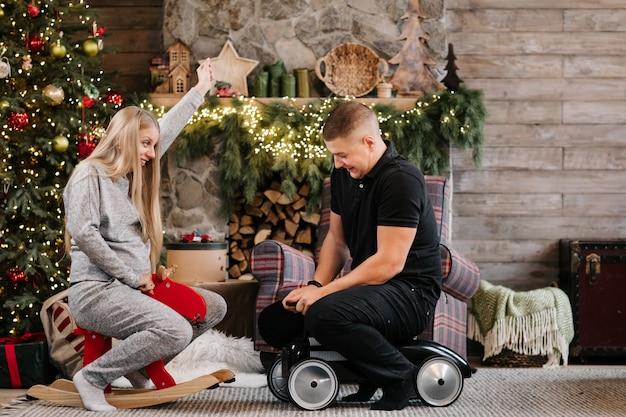 Adorable matrimonio pareja embarazada cerca del árbol de navidad y chimenea en casa