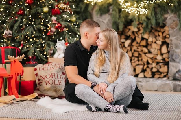 Adorable matrimonio se sienta cerca del árbol de navidad y la chimenea en casa