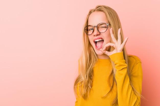Adorable mujer adolescente guiña un ojo y tiene un gesto bien con la mano.