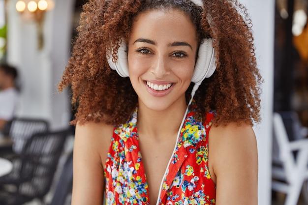 Adorable mujer afroamericana con expresión feliz, satisfecha de escuchar música agradable en auriculares, vestida con blusa brillante, tiene una amplia sonrisa.