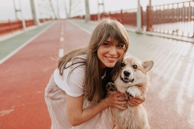 Adorable mujer con cabello castaño sonriendo con su perro mientras camina por la ciudad de la mañana