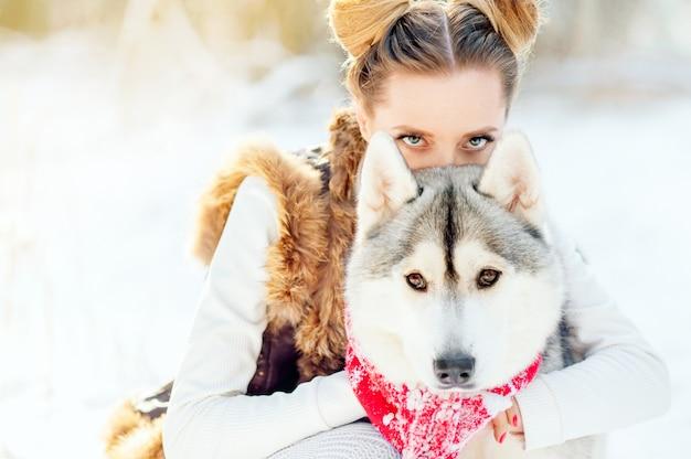 Adorable mujer caucásica pasar tiempo al aire libre disfrutando del clima helado con su mascota husky. foto de bastante jovencita vestida de invierno, mirada penetrante de una niña y un perro
