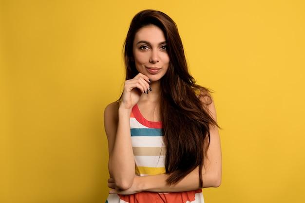 Adorable mujer encantadora con cabello largo castaño con vestido brillante de verano posando con una sonrisa adorable.