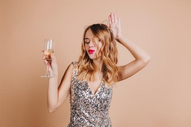 Adorable mujer con expresión de cara de besos sosteniendo una copa de champán en el evento de año nuevo