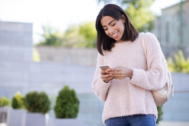 Adorable mujer glamorosa y tranquila que usa su teléfono inteligente y wifi gratuito para leer sus cartas y responderlas de inmediato