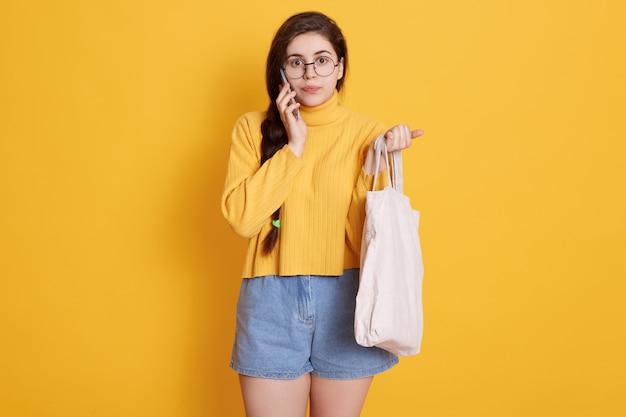 Adorable mujer morena con suéter amarillo y corto, sosteniendo la bolsa en la mano, hablando con su amiga a través de un teléfono inteligente moderno
