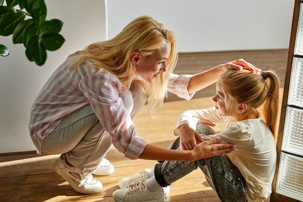 Adorable mujer y niña sentada hablando en el suelo en casa, linda madre e hija hablan, sonríen, reciben apoyo