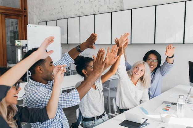 Adorable mujer con peinado rubio corto golpeando las manos con su colega africana. foto interior de compañeros de trabajo alegres celebrando el comienzo de las vacaciones en el lugar de trabajo.