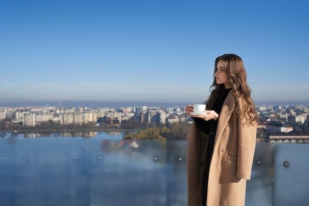 Adorable mujer de pie en el balcón con una taza de café