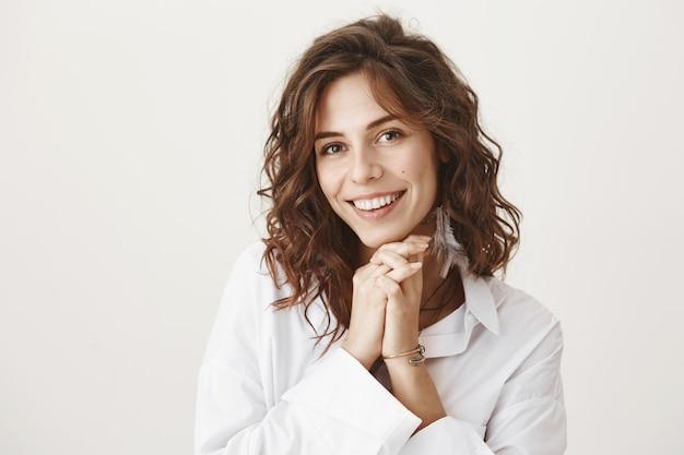 Adorable mujer sonriendo y mirando conmovida o agradecida