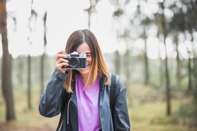 Adorable mujer tomando fotos en el bosque