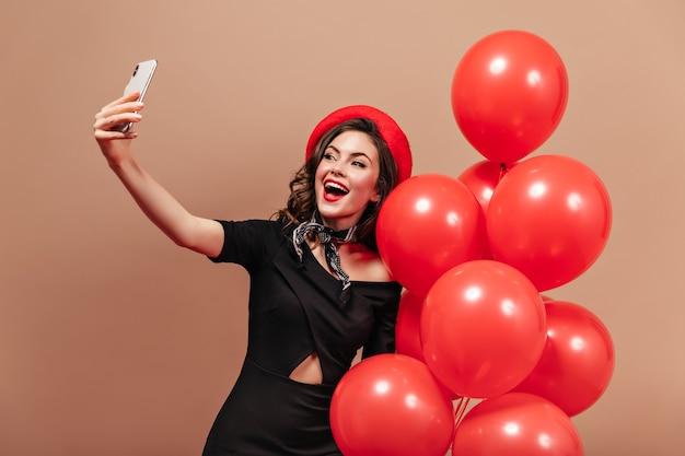 Adorable mujer vestida de negro y boina roja sostiene un teléfono inteligente, hace selfie y posa con globos.
