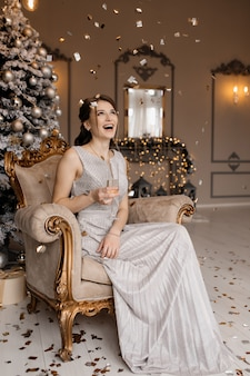 Una adorable mujer con vestido plateado se sienta ante un árbol de navidad con una copa de champán en la mano