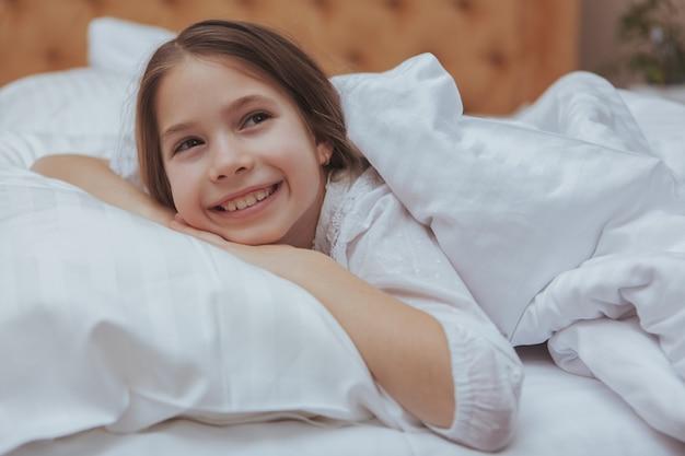 Adorable niña acostada en la cama en su casa