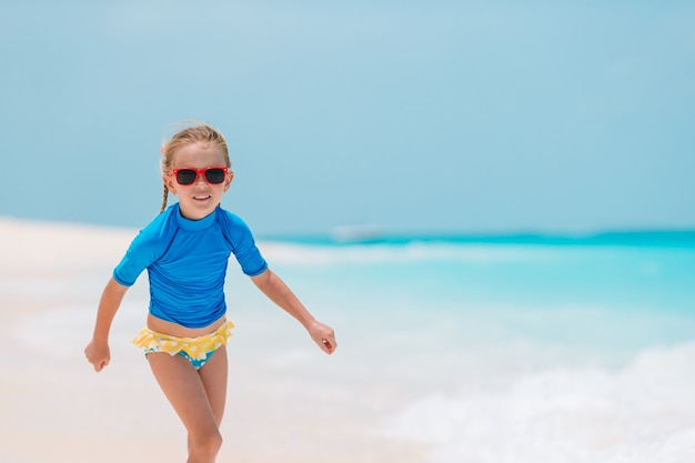 Adorable niña activa en la playa durante las vacaciones de verano