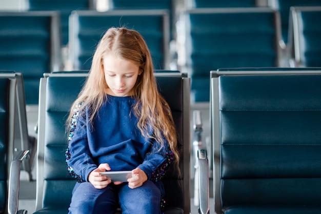 Adorable niña en el aeropuerto cerca de una gran ventana interior