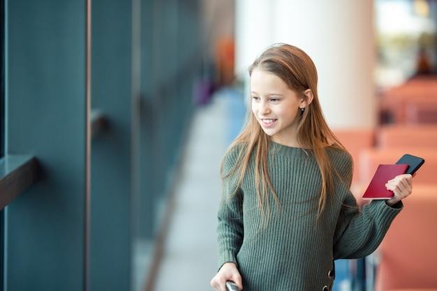 Adorable niña en el aeropuerto en el gran aeropuerto internacional cerca de la ventana