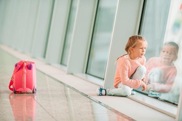 Adorable niña en el aeropuerto con su equipaje esperando el embarque