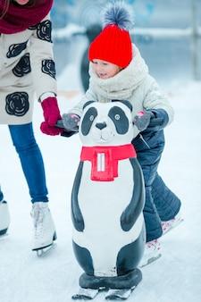 Adorable niña aprendiendo a patinar en la pista de hielo al aire libre
