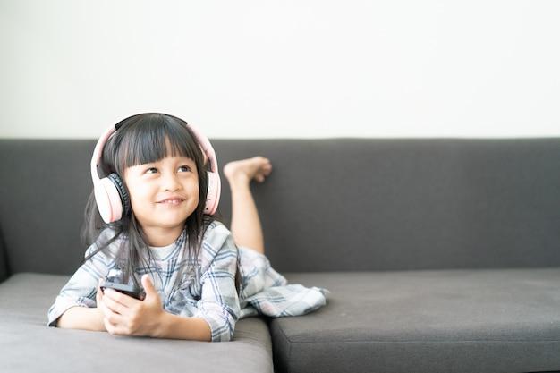 Adorable niña asiática de 4 años está mintiendo y viendo dibujos animados en el teléfono inteligente en el sofá con momento feliz