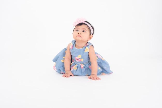 Adorable niña asiática es retrato en pared blanca