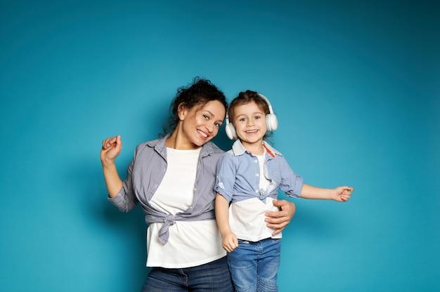 Adorable niña con auriculares bailando cerca de su madre abrazándola sobre una superficie azul con espacio de copia