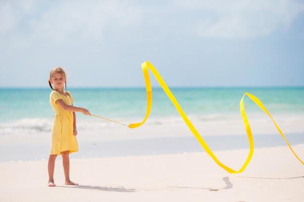 Adorable niña bailando con cinta gimnástica amarilla en la playa