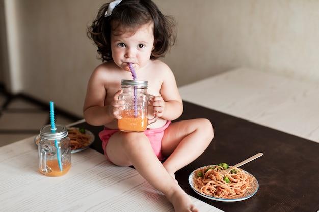 Adorable niña bebiendo jugo