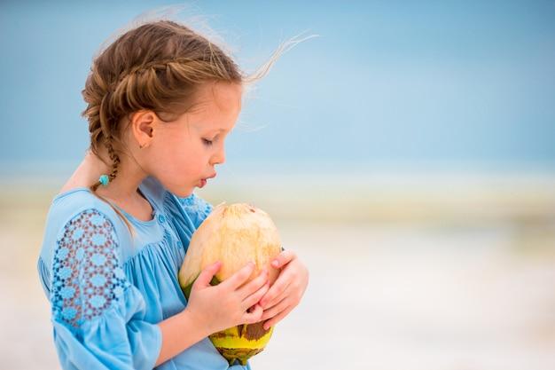 Adorable niña bebiendo leche de coco en la playa