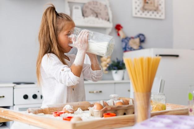 Adorable niña bebiendo leche